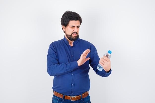 Jonge man die een waterfles vasthoudt en de hand ernaartoe uitstrekt in een blauw shirt en spijkerbroek en er serieus uitziet, vooraanzicht.