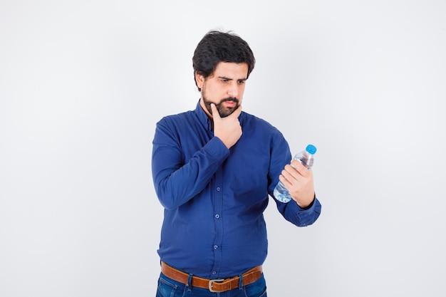 Jonge man die een waterfles vasthoudt en de hand op de kin houdt in een blauw shirt en spijkerbroek en er gefocust uitziet, vooraanzicht.