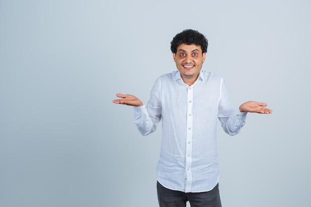 Jonge man die een weegschaalgebaar maakt in een wit overhemd, een broek en er vrolijk uitziet. vooraanzicht.