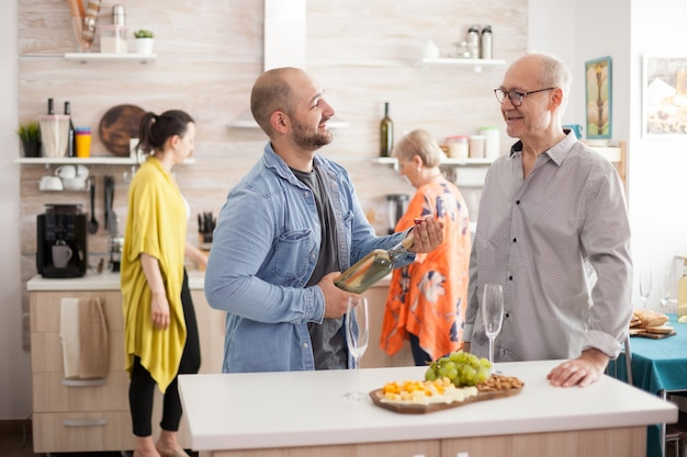 Jonge man die een wijnfles vasthoudt terwijl hij met zijn oude vader in de keuken praat. moeder bereidt lunch voor familie voor.