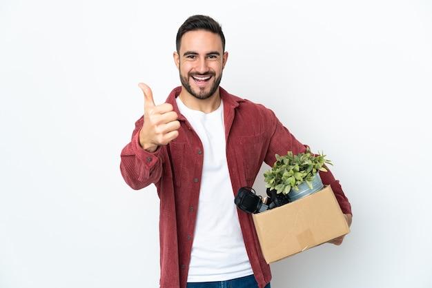 Jonge man die een zet doet terwijl hij een doos vol dingen oppakt die op een witte muur met duimen omhoog worden geïsoleerd omdat er iets goeds is gebeurd