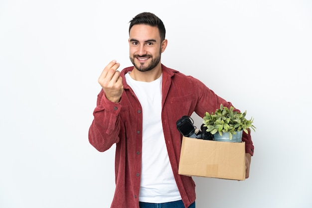 Jonge man die een zet doet terwijl hij een doos vol dingen oppakt die op een witte muur worden geïsoleerd en geldgebaar maken