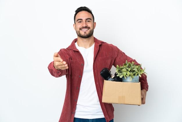 Jonge man die een zet doet terwijl hij een doos vol dingen oppakt die op een witte muur worden geïsoleerd, handen schudden voor het sluiten van een goede deal