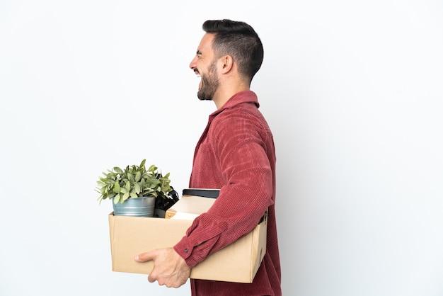 Jonge man die een zet doet terwijl hij een doos vol dingen oppakt die op een witte muur worden geïsoleerd, lachend in zijpositie