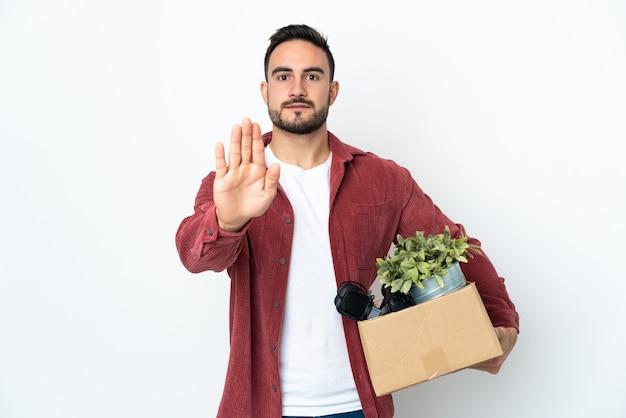 Jonge man die een zet doet terwijl hij een doos vol dingen oppakt die op een witte muur worden geïsoleerd, stopgebaar maken