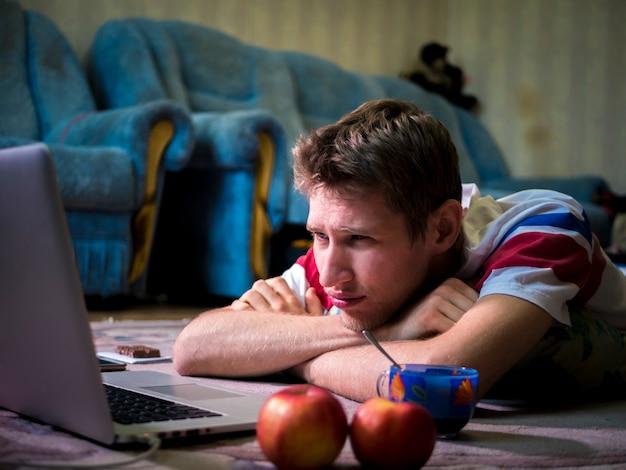 Jonge man die en het letten op op film ligt die zijn laptop thuis met behulp van