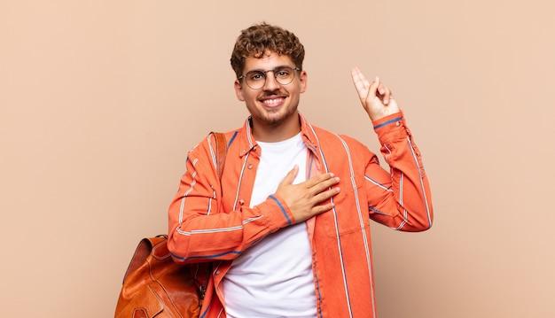 Jonge man die er gelukkig, zelfverzekerd en betrouwbaar uitziet, glimlachend en overwinningsteken toont, met een positieve instelling. student concept