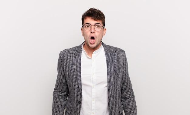 Jonge man die erg geschokt of verrast kijkt, starend met open mond en zegt wow