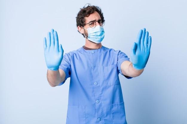 Jonge man die ernstig, ongelukkig, boos en ontstemd kijkt en de toegang verbiedt of stop zegt met beide open handpalmen. coronavirus concept