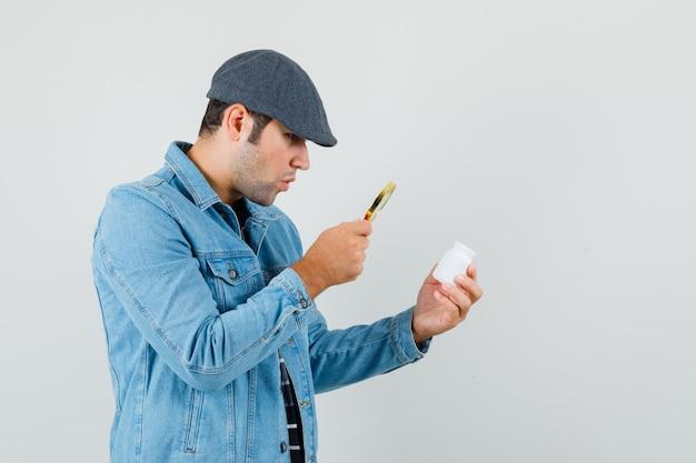 Jonge man die fles pillen met vergrootglas in jasje, glb kijkt en gericht kijkt.