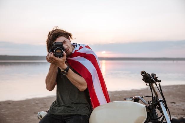 Jonge man die foto met camera maakt zittend op zijn motorfiets buitenshuis