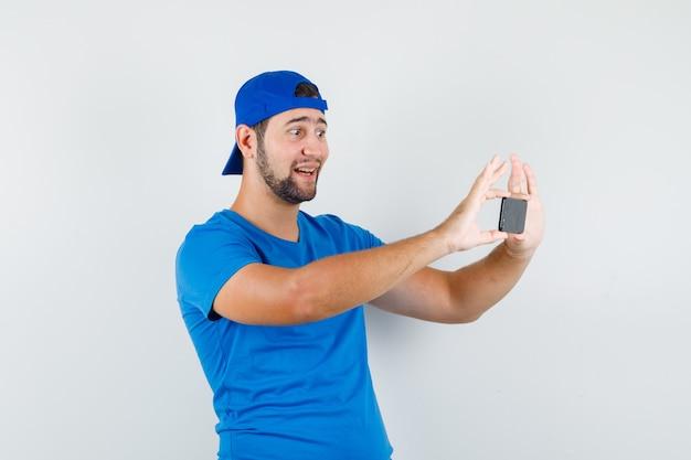 Jonge man die foto op mobiele telefoon in blauw t-shirt en pet en op zoek vrolijk