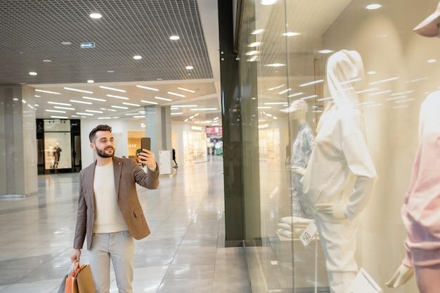 Jonge man die foto's maakt van nieuwe kleren op etalagepop in groot display
