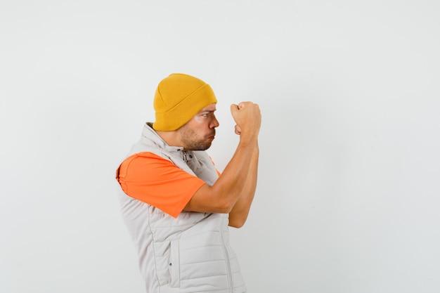 Jonge man die gebalde vuisten in t-shirt, jasje, hoed opheft en er sterk uitziet