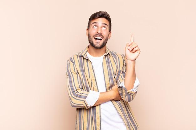 Jonge man die gelukkig glimlacht en zijwaarts kijkt, zich afvraagt, denkt of een idee heeft