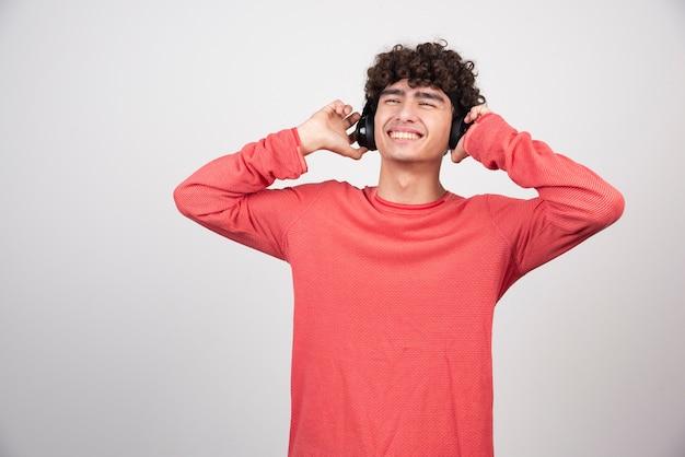 Jonge man die gelukkig naar muziek luistert met een koptelefoon.