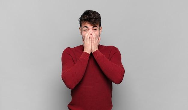 Jonge man die gelukkig, vrolijk, gelukkig en verrast kijkt en de mond bedekt met beide handen