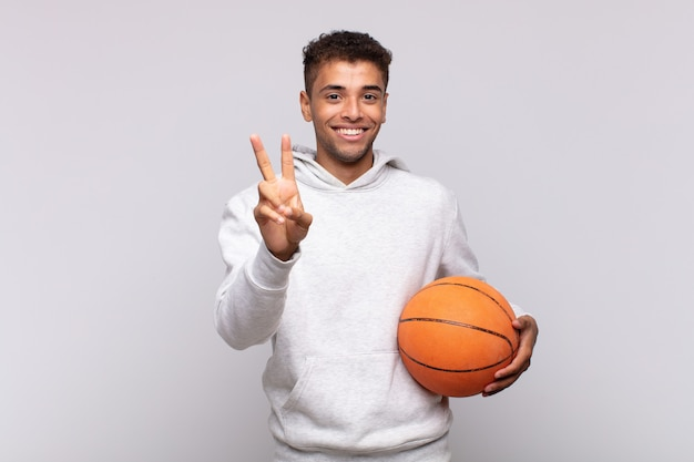 Jonge man die gelukkig, zorgeloos en positief glimlacht en kijkt, met één hand overwinning of vrede gebaart. mand concept