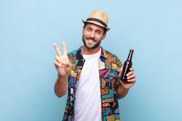 Jonge man die gelukkig, zorgeloos en positief glimlacht en kijkt, met één hand overwinning of vrede gebaart. vakantie concept