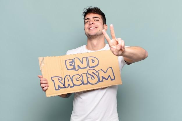 Jonge man die gelukkig, zorgeloos en positief glimlacht en kijkt, met één hand overwinning of vrede gebaart