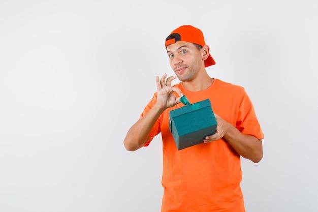 Jonge man die geschenkdoos in oranje t-shirt en pet probeert te openen en nieuwsgierig kijkt