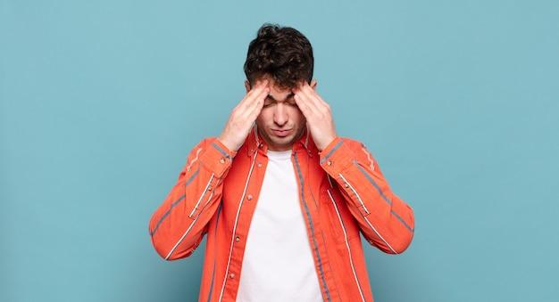 Jonge man die gestrest en gefrustreerd kijkt, onder druk werkt met hoofdpijn en last heeft van problemen