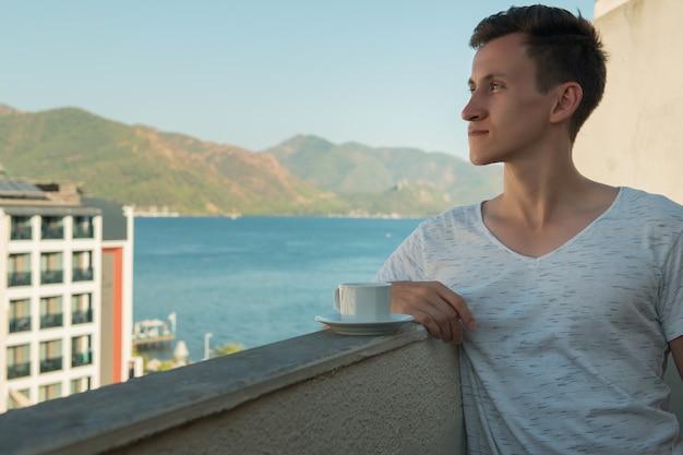 Jonge man die geurige koffie drinkt terwijl hij op het balkon van haar kamer in het hotel staat