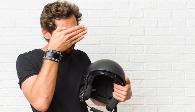 Jonge man die gezicht bedekt met beide handen en zegt nee! afbeeldingen weigeren of foto's verbieden