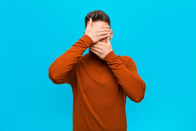 Jonge man die gezicht bedekt met beide handen nee zeggen tegen de camera! afbeeldingen weigeren of foto's over de blauwe muur verbieden