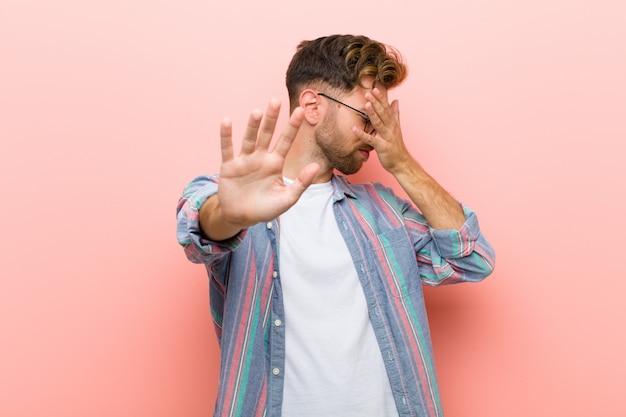 Jonge man die gezicht bedekt met de hand en andere hand vooraan zet om de camera te stoppen, weigert foto's of foto's
