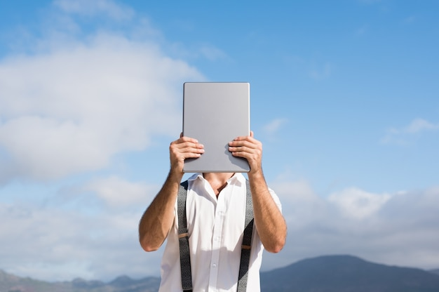 Jonge man die gezicht bedekt met digitale tablet