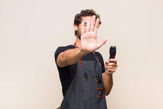 Jonge man die gezicht bedekt met hand en andere hand naar voren zet, foto's of afbeeldingen weigert