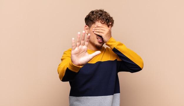 Jonge man die gezicht bedekt met hand en andere hand naar voren zet om te stoppen, foto's of afbeeldingen weigeren