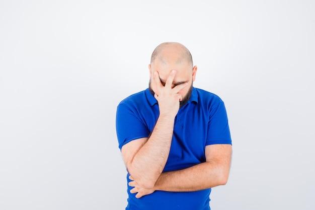 Jonge man die gezicht bedekt met hand in blauw shirt en boos kijkt. vooraanzicht.