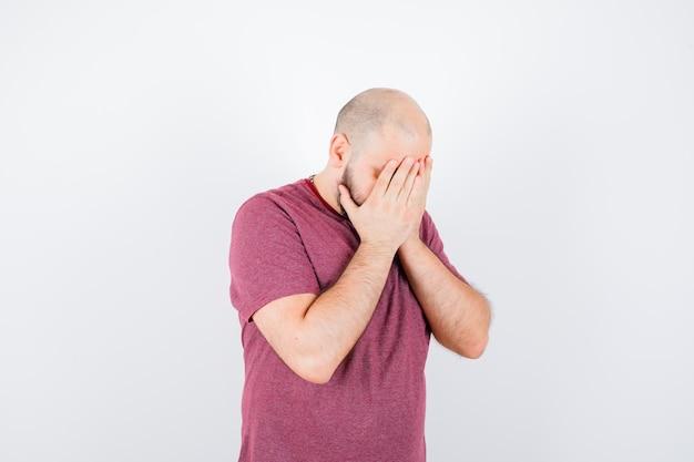Jonge man die gezicht bedekt met handen in roze t-shirt en boos kijkt, vooraanzicht.