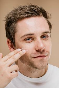 Jonge man die gezichtscrème aanbrengt