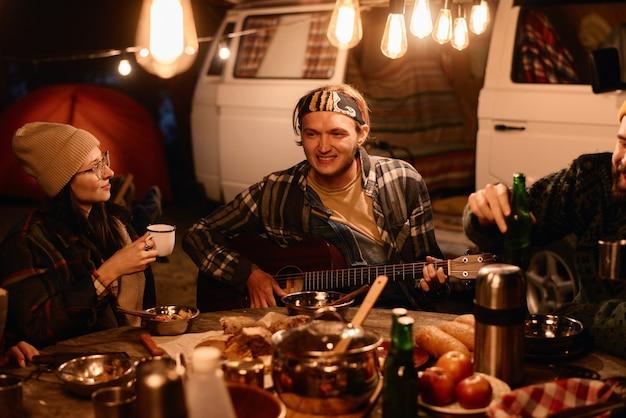 Jonge man die gitaar speelt, aan tafel zit met zijn vrienden en 's avonds dineert op een picknick