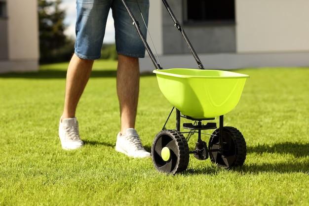 Jonge man die gras zaait in de achtertuin