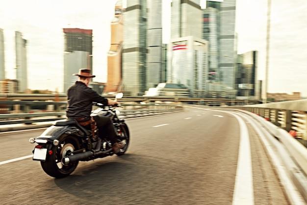 Jonge man die grote fiets berijdt, motorfiets op stadsweg tegen stedelijke en stadsbouwscène. bewegingsonscherpte