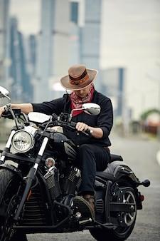 Jonge man die grote fiets berijdt, motorfiets op stadsweg tegen stedelijke en stadsbouwscène