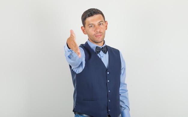 Jonge man die hand aanbiedt om in kostuum, jeans te schudden en er vriendelijk uit te zien.