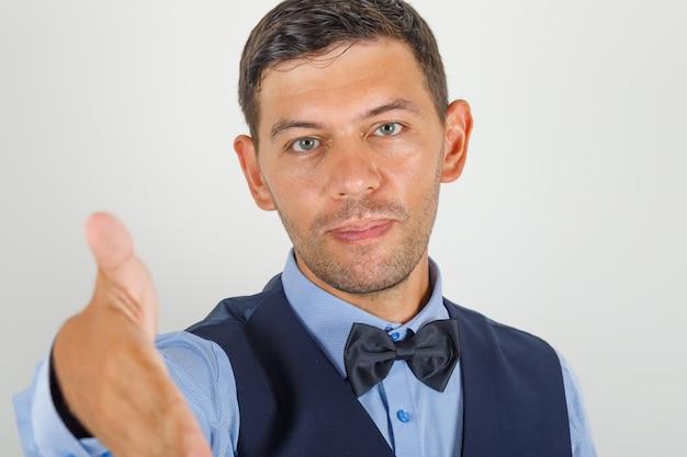 Jonge man die hand aanbiedt om in pak te schudden en er vriendelijk uit te zien