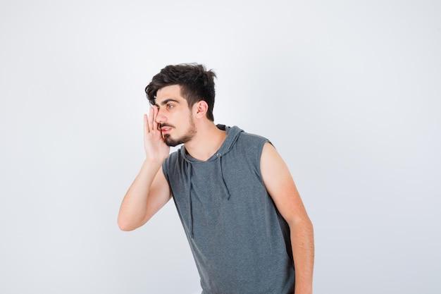 Jonge man die hand in de buurt van mond houdt terwijl hij iemand in een grijs t-shirt belt en er serieus uitziet?