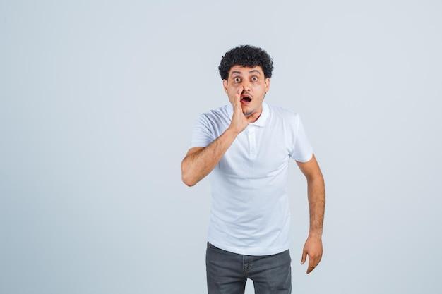 Jonge man die hand in de buurt van mond houdt terwijl hij iemand in wit t-shirt en spijkerbroek roept en verrast kijkt, vooraanzicht.