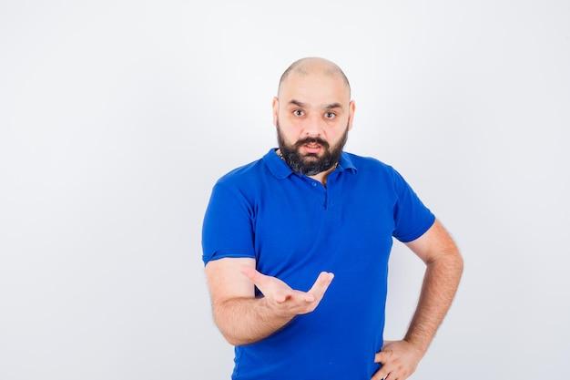 Jonge man die hand op een agressieve manier opsteekt terwijl hij in een blauw shirt praat en er nerveus uitziet. vooraanzicht.