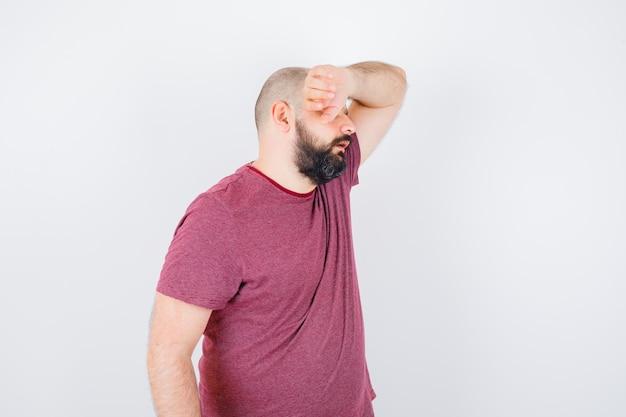 Jonge man die hand op het voorhoofd houdt in roze t-shirt en er uitgeput uitziet.