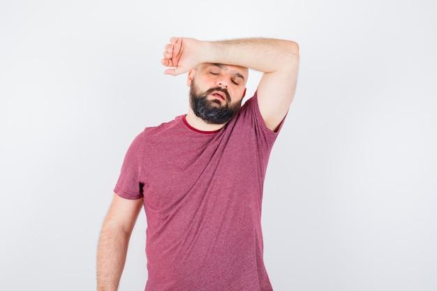 Jonge man die hand op het voorhoofd in roze t-shirt houdt en er moe uitziet, vooraanzicht.