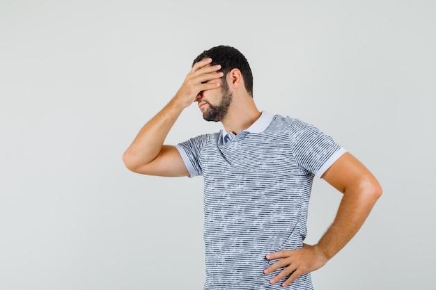 Jonge man die hand op ogen in t-shirt houdt en beschaamd kijkt. vooraanzicht.