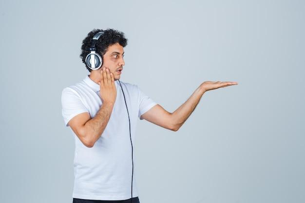 Jonge man die hand op wang houdt, palm opzij spreidt in wit t-shirt en geschokt kijkt. vooraanzicht.
