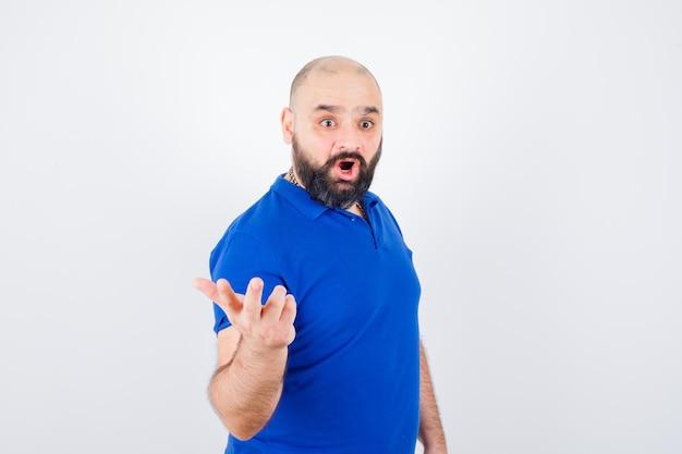 Jonge man die hand opsteekt met open palm opzij terwijl hij in een blauw shirt praat en gealarmeerd kijkt, vooraanzicht.